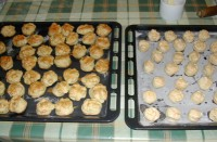 Túrós pogácsa - A kisült pogácsák és a sütésre váró pogácsák tepsije.